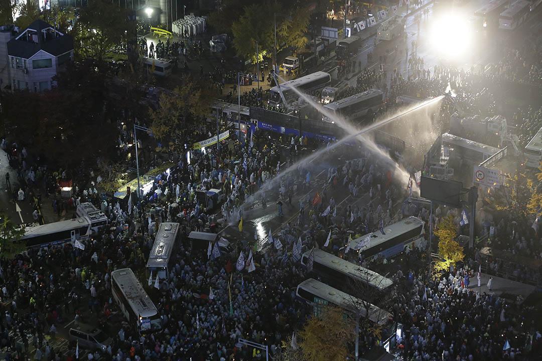 2015年11月14日,首爾警方動用水炮驅散參與反政府遊行的示威者。攝:Ahn Young-joon/AP