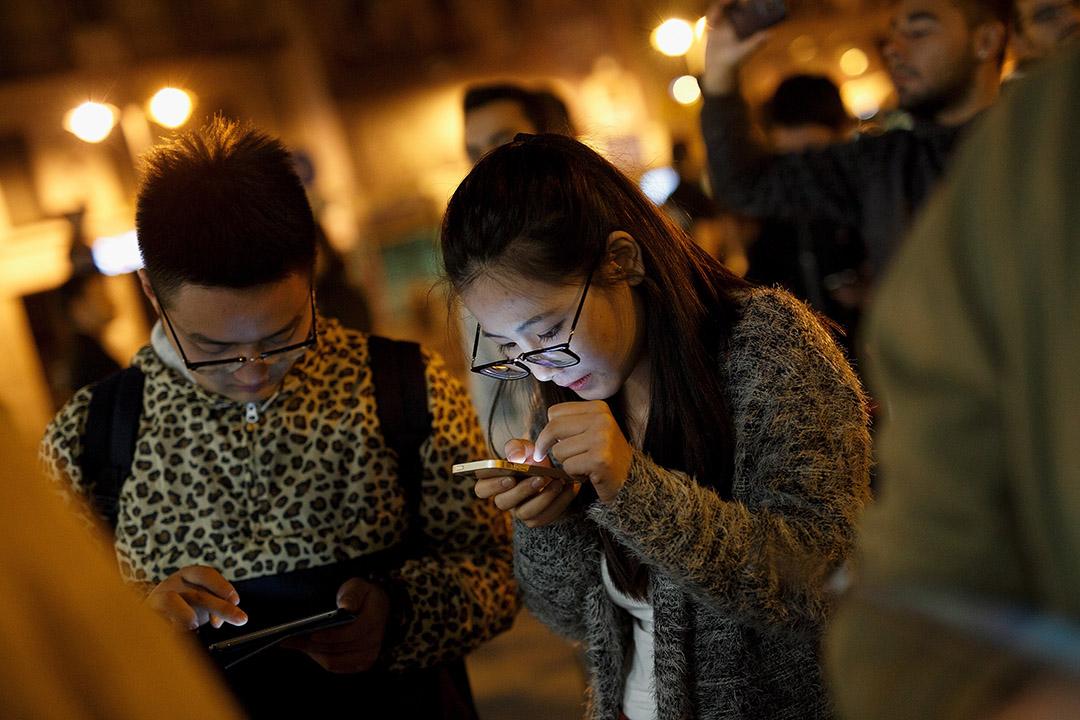 圖為一對男女在西班牙街頭使用智能電話。攝:Blazquez Dominguez/GETTY
