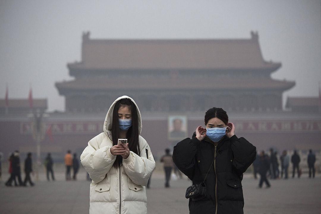 2015年12月9日,中國北京,兩名女子因空氣污染而於參觀天安門廣場時戴上口罩。攝:Kevin Frayer/GETTY