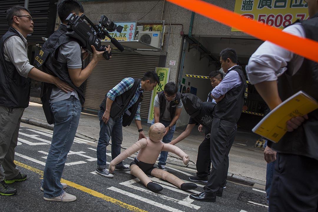 2015年10月19日,一名內地遊客懷疑因為購物問題被毆打至重傷,其後死亡。警方將其中一名疑犯──44歲的港人導遊胡彥南,押返紅磡案發現場重組案情。攝:羅國輝/端傳媒