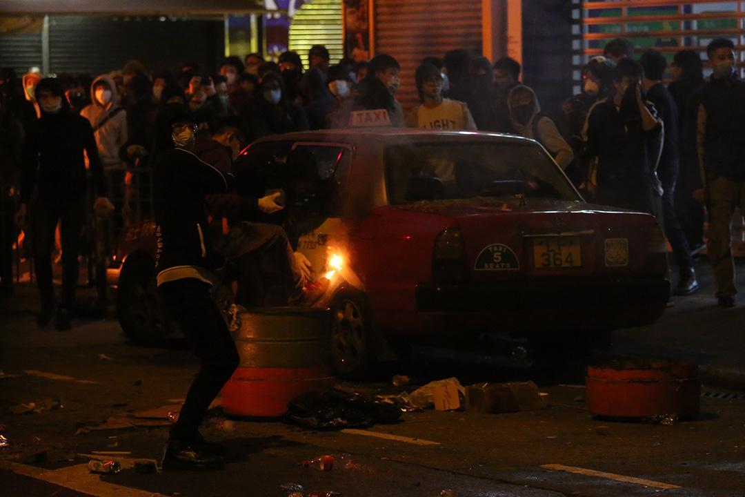 2016年2月9日清晨約七時,示威者在旺角街道多處地方焚燒雜物,有停泊在路邊的士被破壞。攝:盧翊銘/端傳媒
