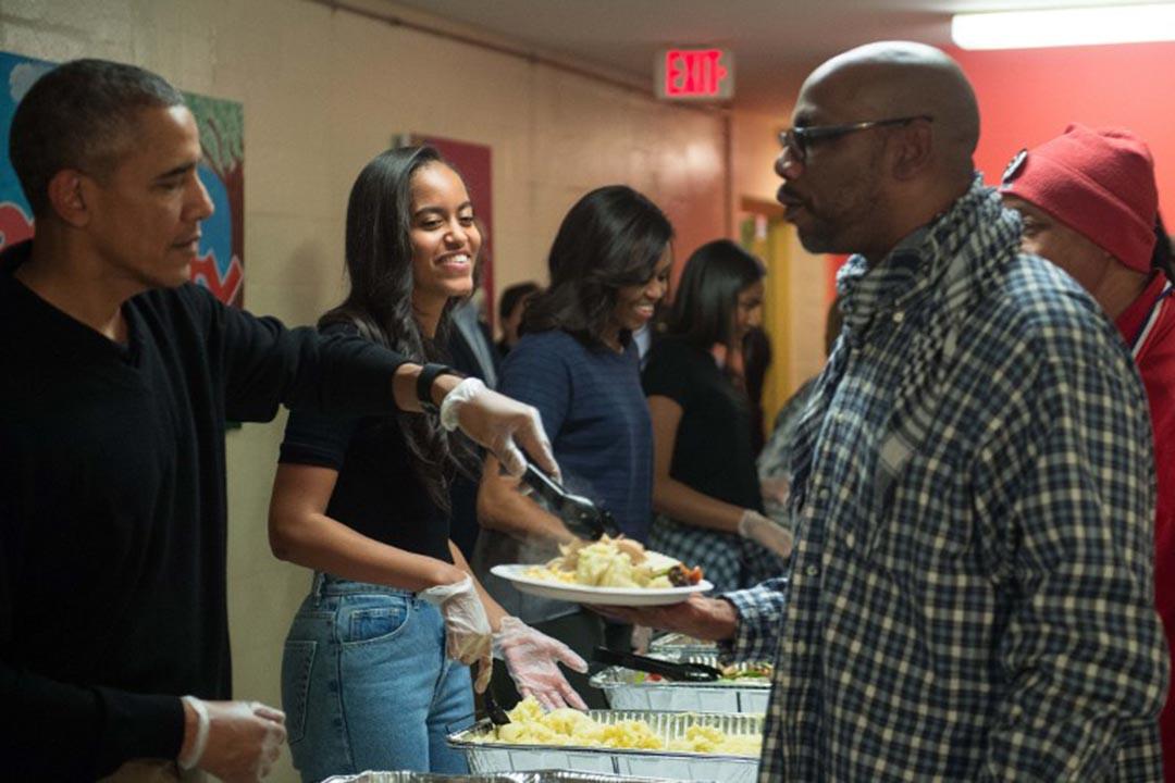 奧巴馬與女兒來到華盛頓「哥倫比亞特區中心廚房」,和那裏的社工一起,為無家可歸者準備飯菜。攝:NICHOLAS KAMM/AFP