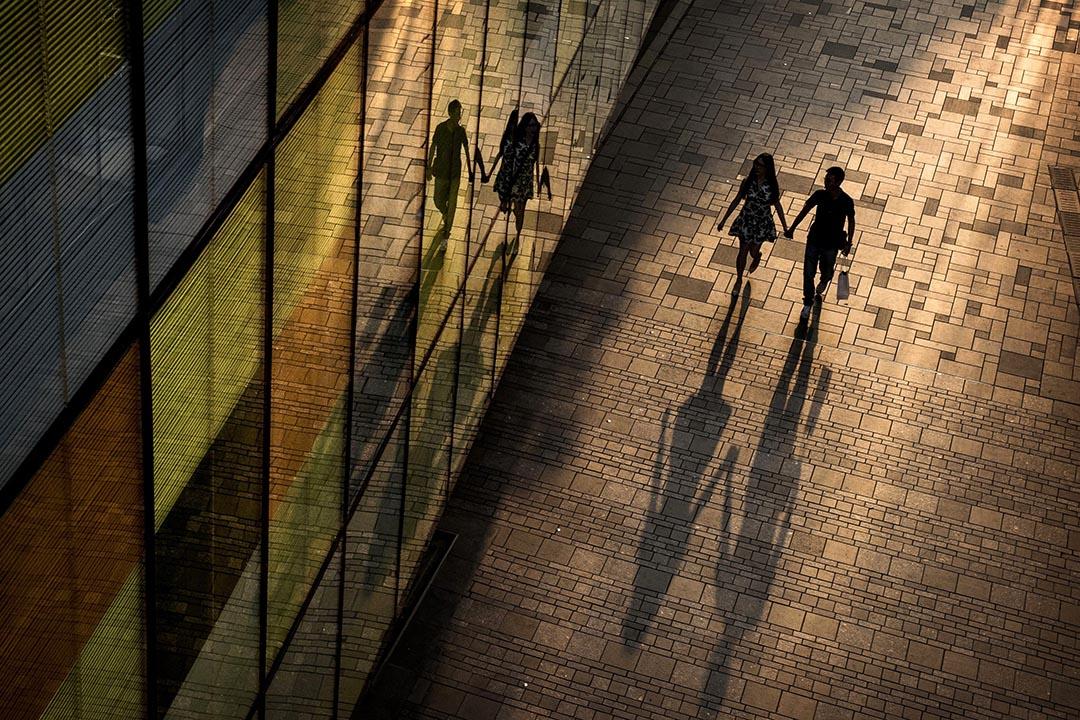 一對情侶在北京的商場外走過。攝:Kevin Frayer/Getty