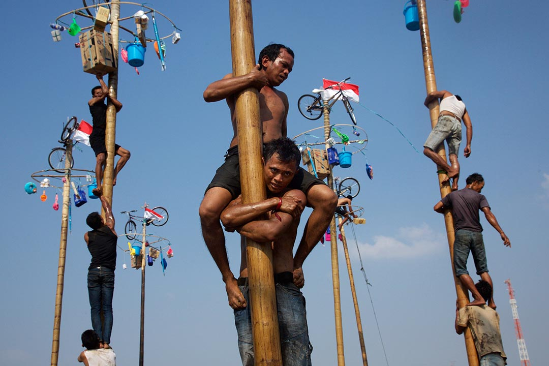 印尼雅加達一批參加者鬥快攀爬至檳榔柱頂端。