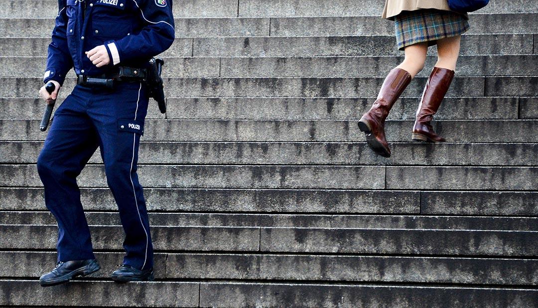 2016年1月9日,德國科隆,一名女性與警察在中央火車站和科隆大教堂之間的樓梯上擦身而過。攝:Sascha Schuermann/Getty Images