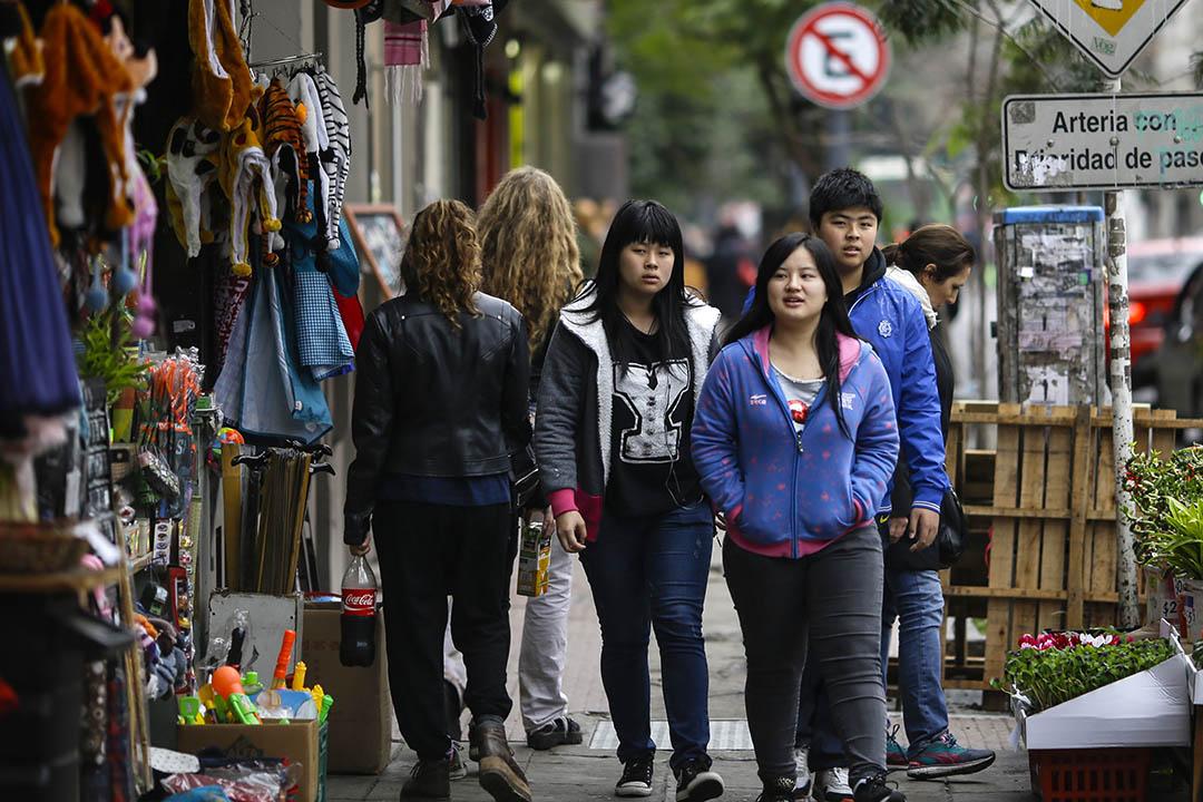 聚居區的年輕華人,他們最常見的工作是在超市裏幫助打理家族生意。攝:Anibal Greco/端傳媒