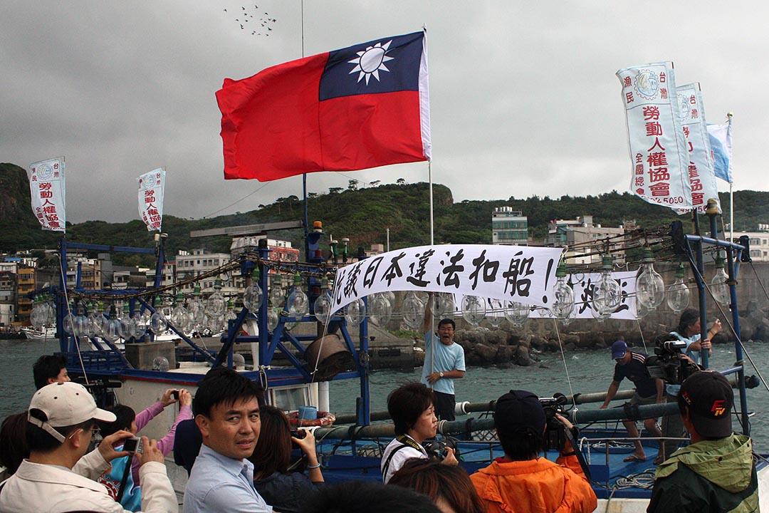台灣的右翼分子在台灣野柳的一個漁港舉起揮動國旗。攝 : Yu Wei-Feng/AFP