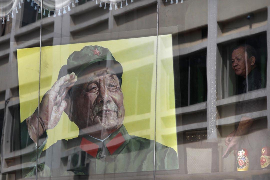 一名男人在窗旁看著已故中國領導人鄧小平的畫像。攝:Jason Lee/REUTERS