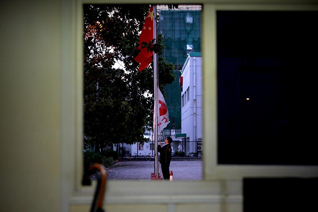 香港亞洲電視的工作人員在大埔廠房降下公司旗幟。攝:盧翊銘/端傳媒