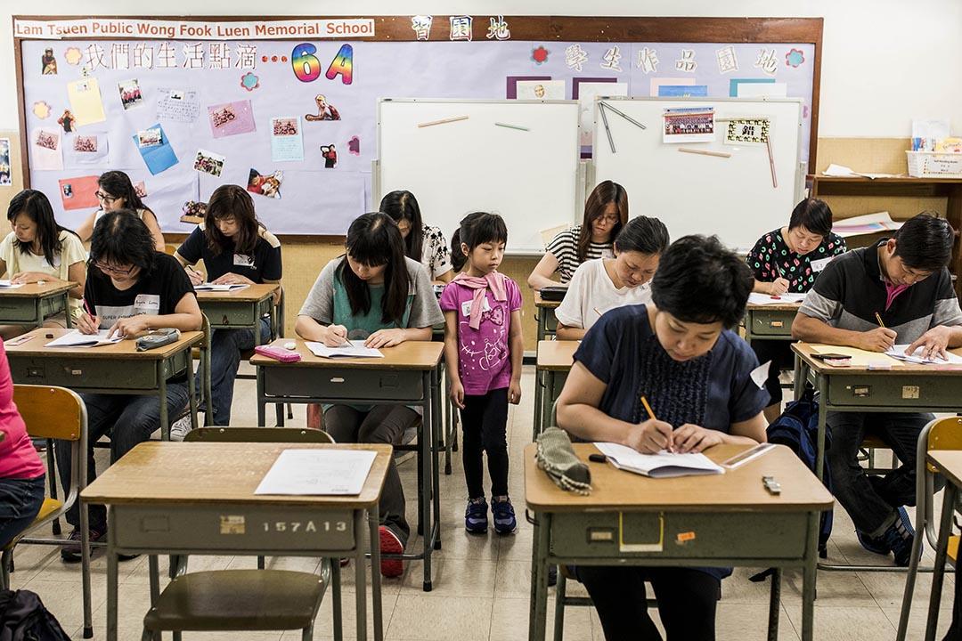 家長參與《端傳媒》的模擬TSA考試,設身處地嘗一嘗孩子的感受,整個過程由小朋友「監考」。攝:Xaume Olleros/端傳媒
