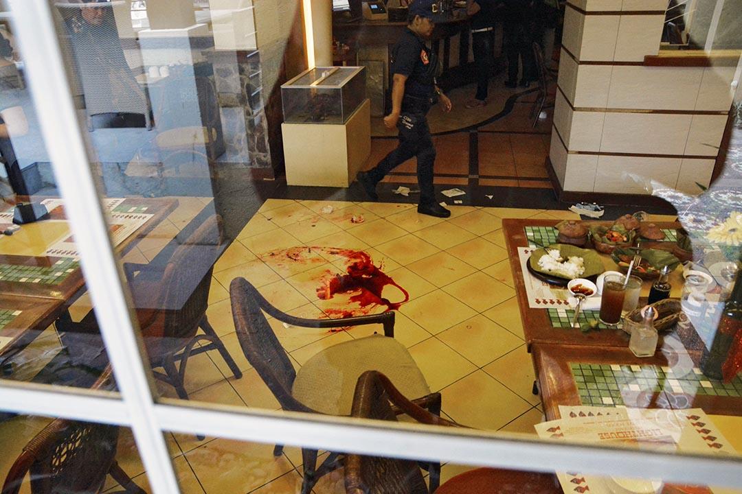 一名菲律賓警察在案發現場走過。攝 : Christian Maningo/端傳媒