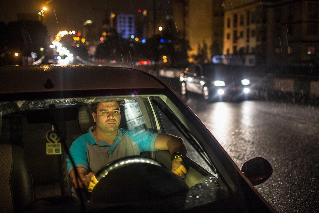 Amin Mokhtari,每晚在德黑蘭駕駛的士。他的正業是在一間旅遊公司擔任英語翻譯。他也在清晨時份從事保安工作。攝:Arash Khamooshi/端傳媒