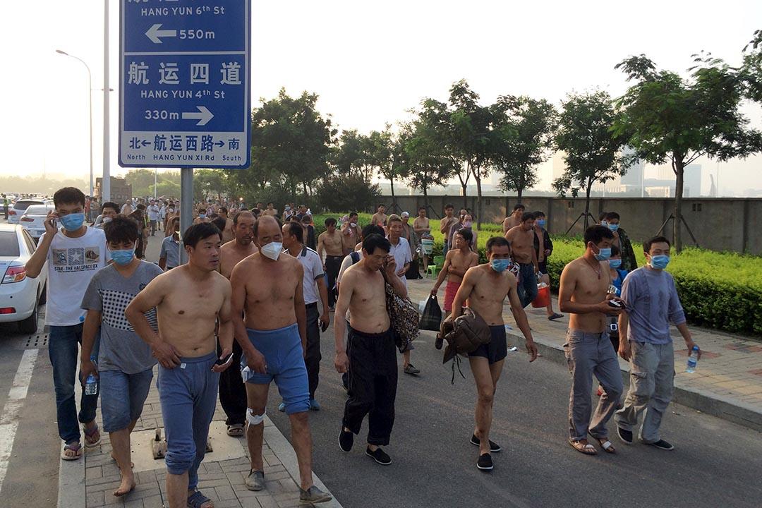 臨近爆炸地點的居民帶着口罩撤往安置點。