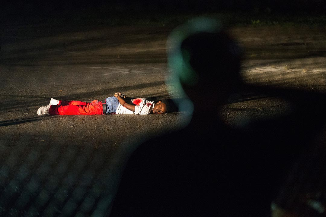 美國密蘇里州弗格森市進行紀念黑人青年布朗(Michael Brown)被槍殺一週年活動期間,民眾在西弗洛裏森特大道上聚集時,一名黑人青年向警員開槍,警員還擊後他中槍倒地。攝 : Scott Olson/GETTY