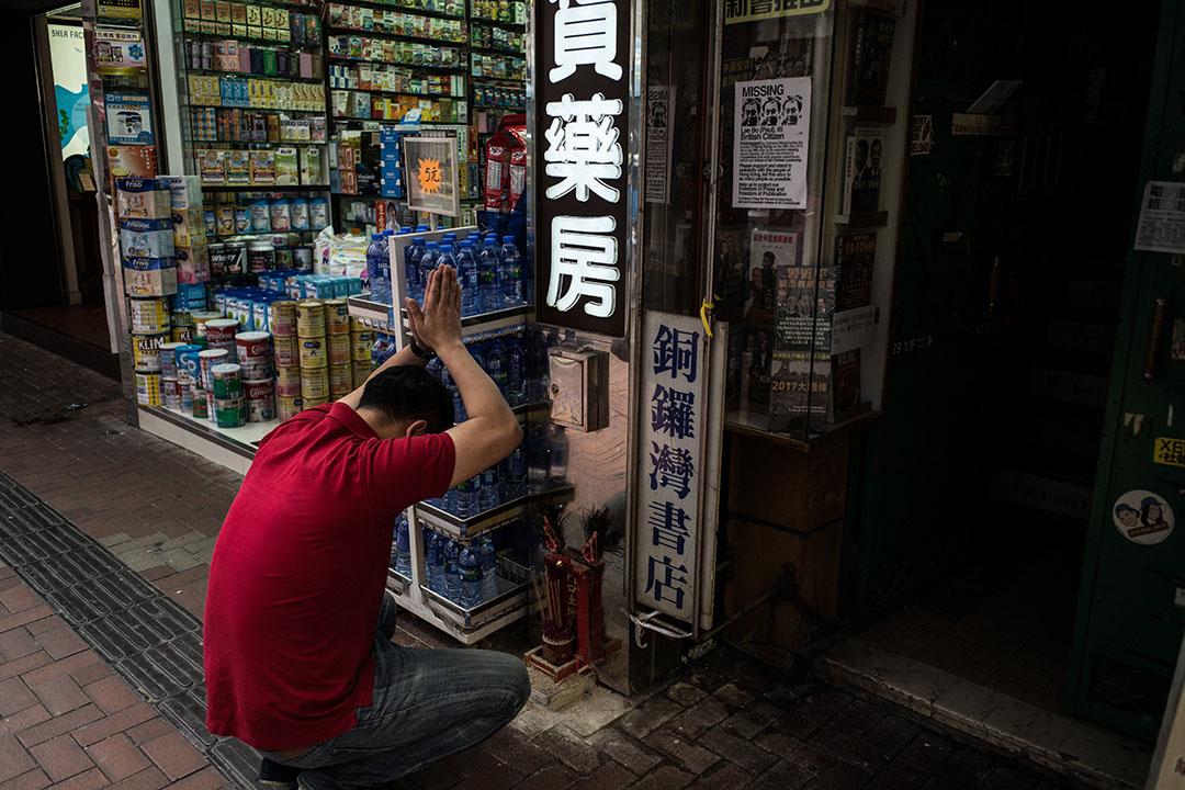 2016年1月19日,一名藥房員工在銅鑼灣書店入口旁拜神。