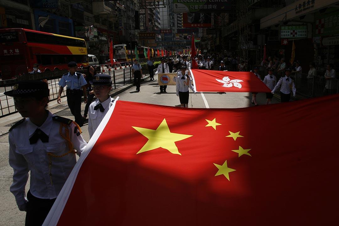 圖為學生制服團體於2009年參與慶祝香港回歸巡遊時拉起中國國旗和香港區旗。 攝:Bobby Yip/Reuters