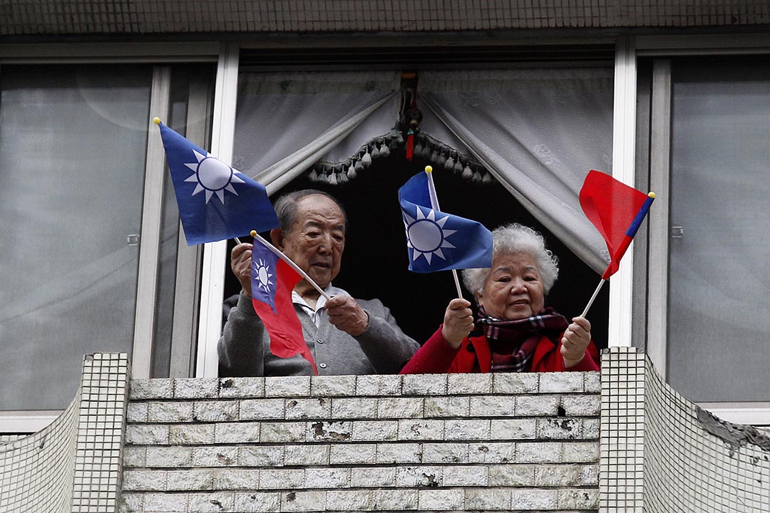 兩名年老的國民黨支持者在一場活動中揮動青天白日滿地紅旗。攝: Pichi Chuang /REUTERS