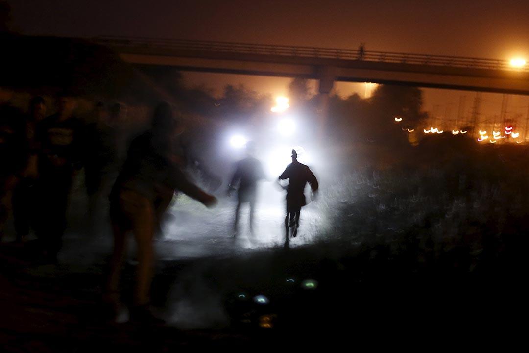 2015年8月5日 法國加來  警察手持電筒追捕企圖通過英法海底隧道偷渡的難民。攝: Juan Medina /REUTERS