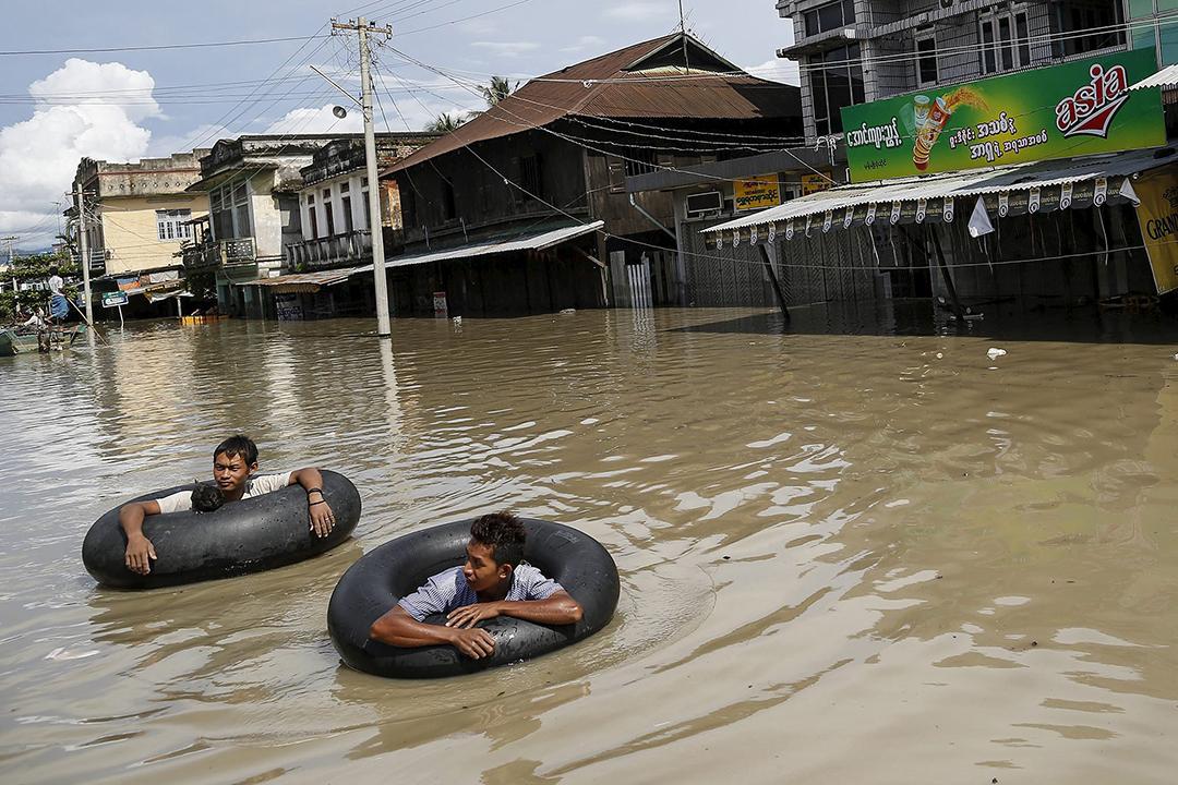洪水淹沒街道,災民用水泡協助游出災區。攝:  Soe Zeya Tun/REUTERS