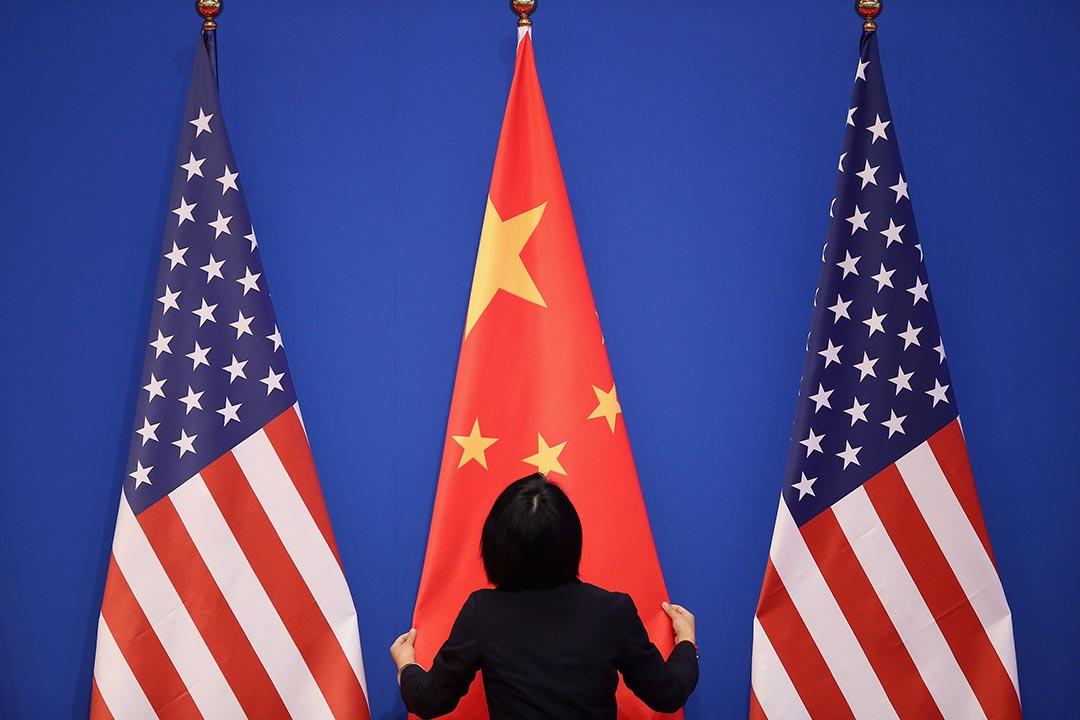 一名工作人員在整理中國國旗。攝:Feng Li/Getty Images
