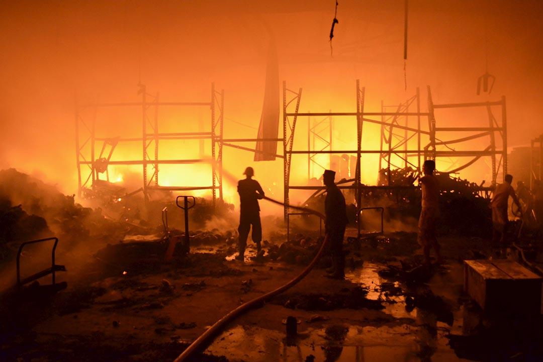 1月6日,也門西北部城市 Houdieda,當天以沙特為首的阿拉伯國家聯軍對也門境內的胡塞武裝組織發起空襲。圖為消防員在為被空襲的建築滅火。攝:Abduljabbar Zeyad/REUTERS