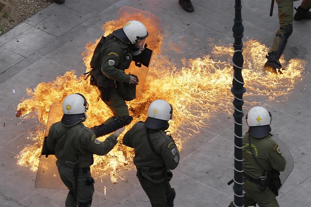 2016年2月4日,雅典,全國24小時大罷工抗議計劃養老金改革,防暴警察被示威者投擲汽油彈。攝:Thanassis  Stavrakis/AP