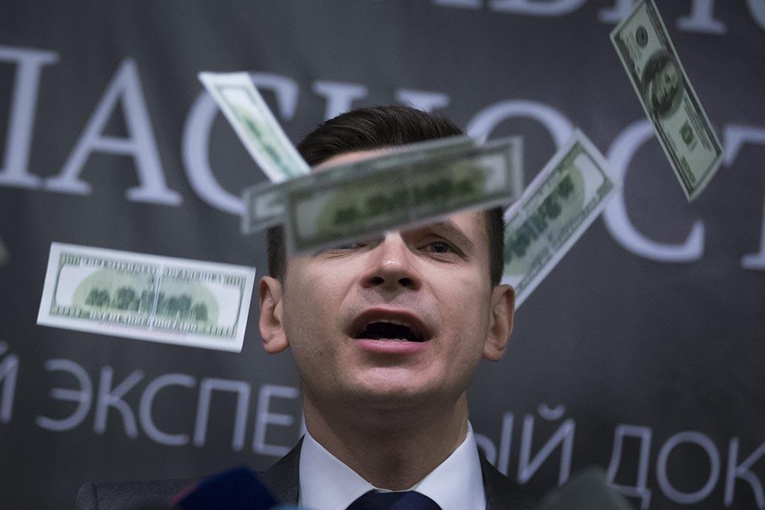 """2016年2月23日,俄羅斯反對派活動人士 Ilya Yashin 在莫斯科發布主題為""""國家安全威脅""""的報導時,遭不明身份者扔假鈔。攝:Alexander Zemlianichenko/AP"""