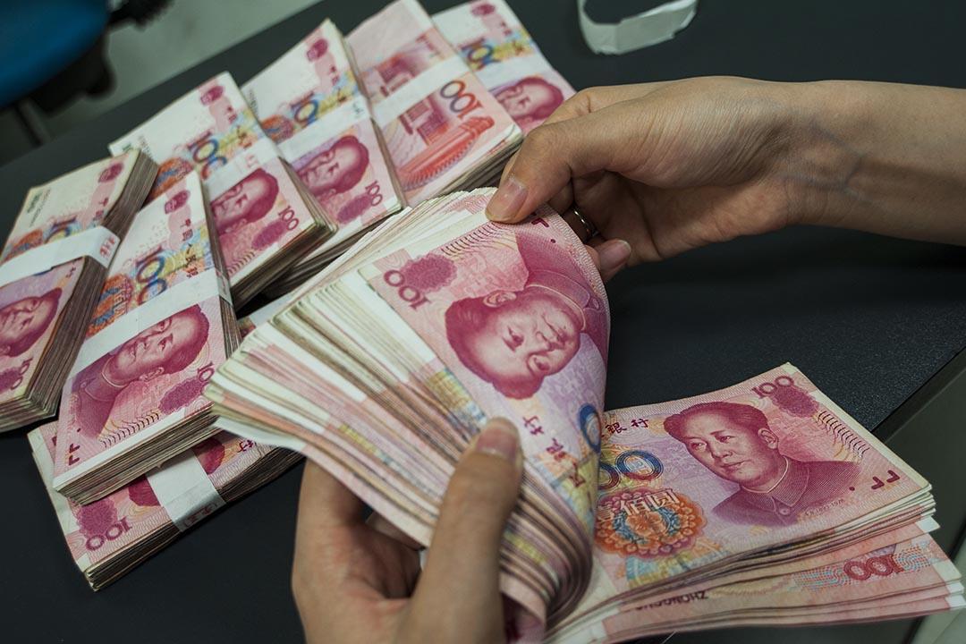 中國建設銀行的職員在點算人民幣。攝:Xu jingbai/AFP