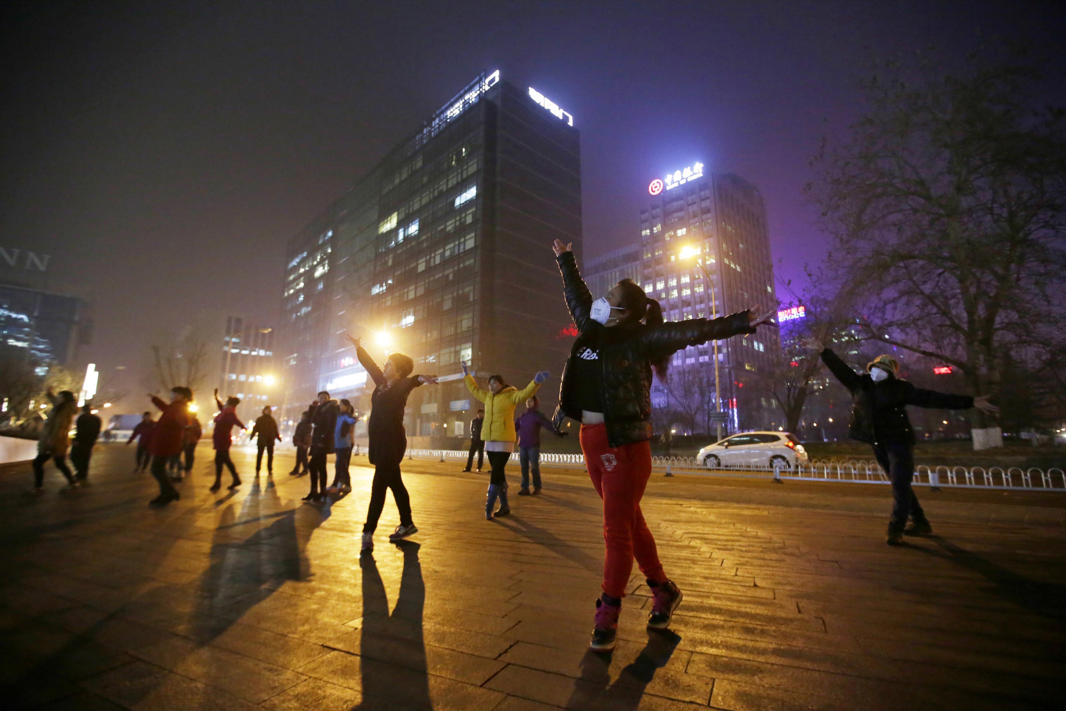 北京一個廣場,大媽在霧霾天氣中跳舞。攝:Jason Lee/REUTERS
