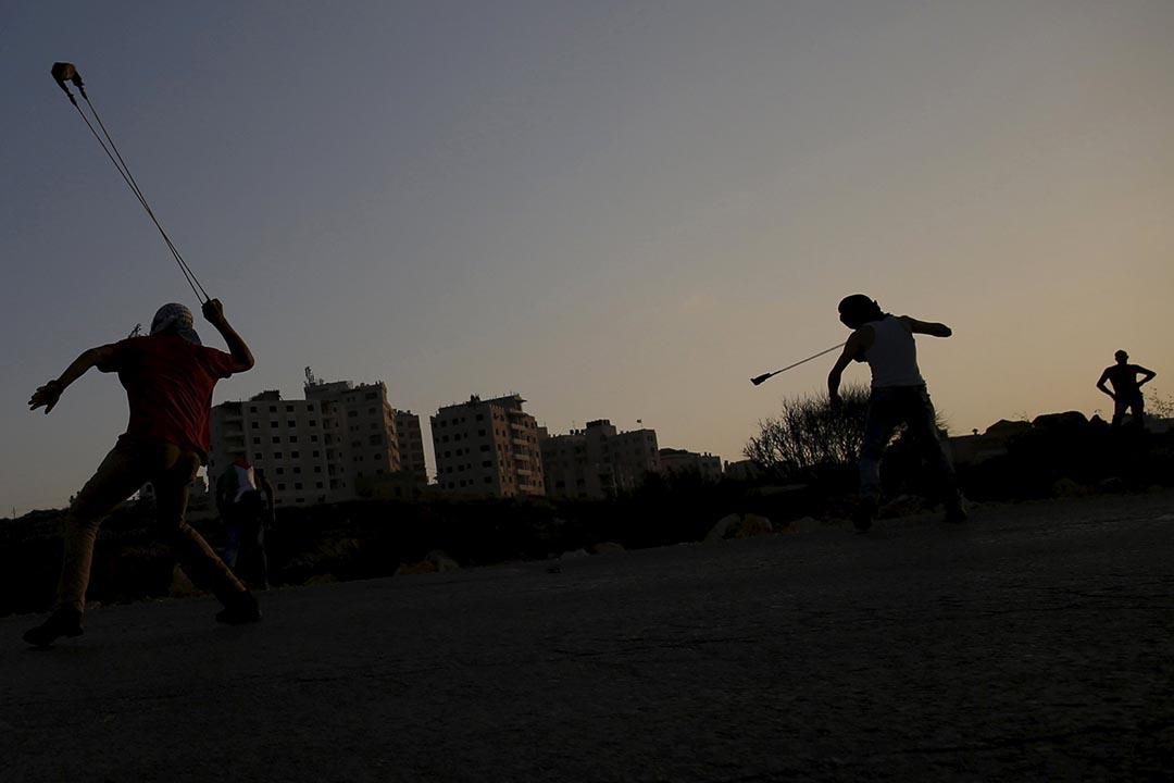 巴勒斯坦人向以色列士兵投擲石頭。攝:Mohamad Torokman / REUTERS