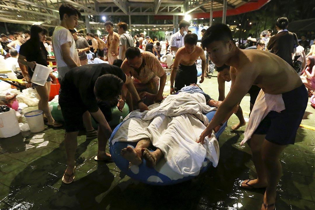 2015年6月27日,台灣新北市八里區八仙樂園發生塵爆意外,圖為傷者被抬走搶救。攝:Wu Chia/REUTERS