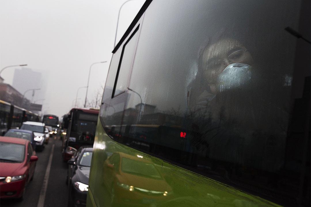 中國北京一輛公共汽車上,乘客戴著口罩望著窗外霧霾天氣。攝: Kevin Frayer/Getty Images
