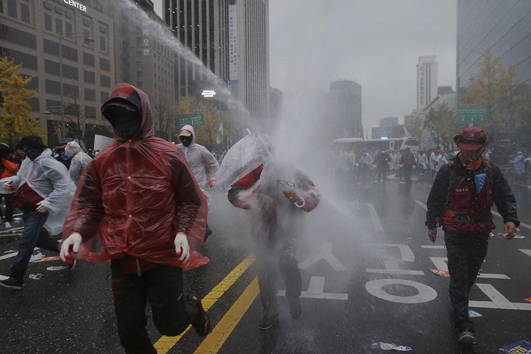 2015年11月14日於南韓首爾,有反政府示威者撐着雨傘,勉強抵擋警方水炮,繼續遊行前往總統府。攝:Ahn Young-joon/AP