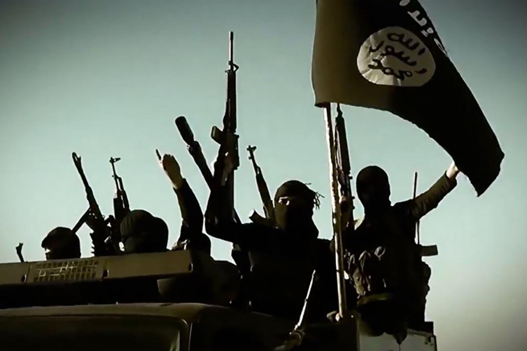 伊斯蘭國聖戰士站在車上高舉武器。攝 : AFP/HO/AL-FURQAN MEDIA