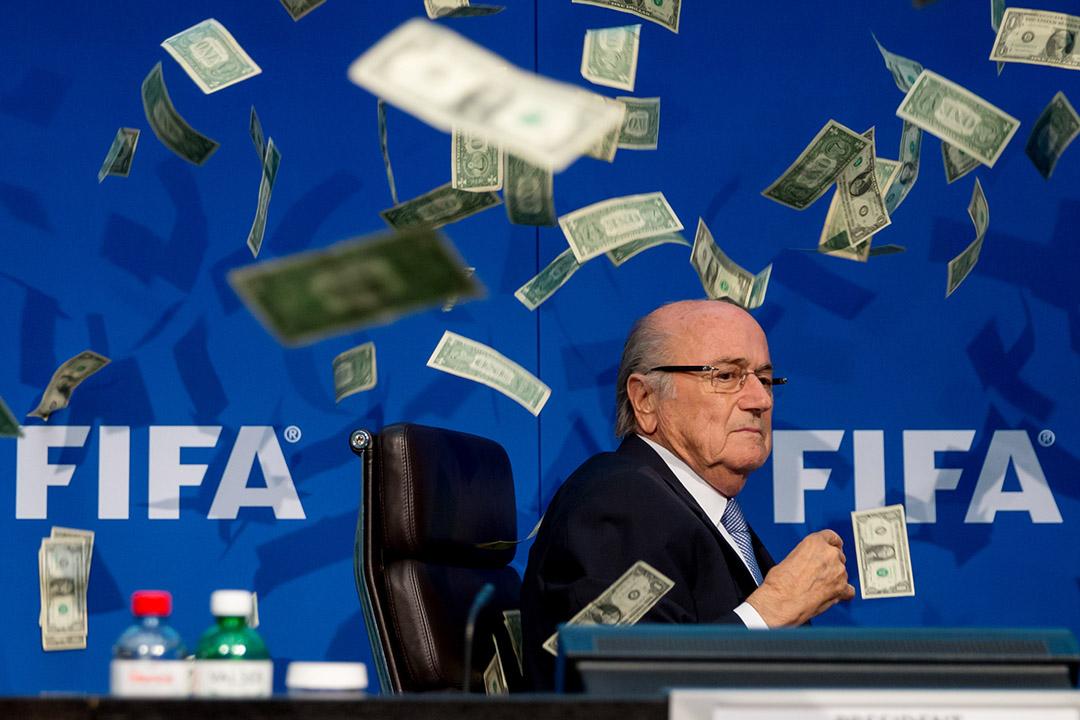 2015年7月20日,瑞士蘇黎世,國際足協主席白禮達出席記者會期間,喜劇演員西蒙·布羅德金(Simon Brodkin)向他扔了一堆美元。攝:Philipp Schmidli/GETTY
