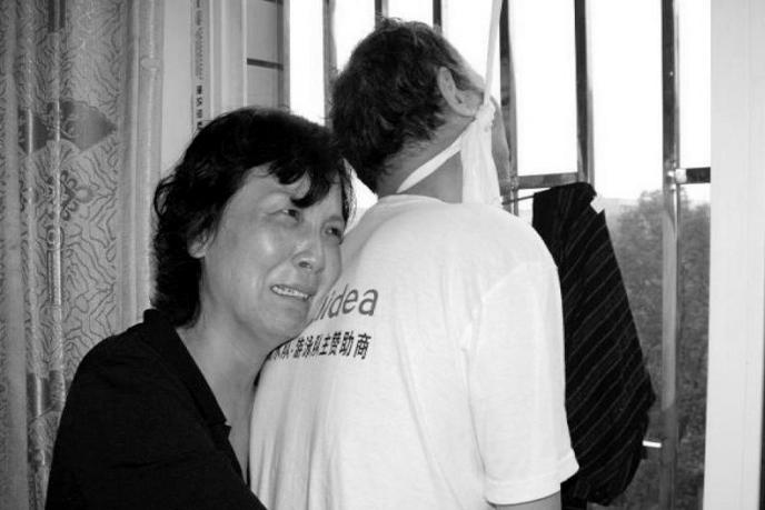 2012年6月6日,中國湖南朝陽市,李旺陽胞妹李旺玲(左)在大祥醫院抱著胞兄李旺陽的屍體。攝:EyePress News via AFP