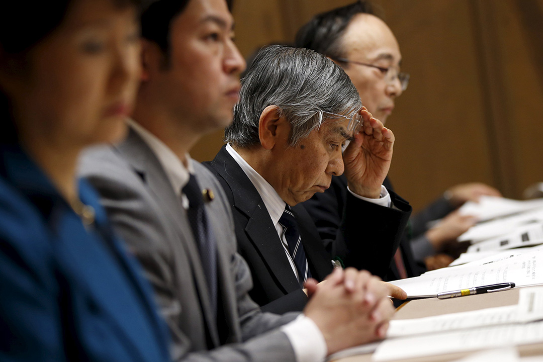 2016年2月18日,日本東京,日本央行行長黑田東彥(右二)在上議院的財政會議上閱讀文件。攝:Toru Hanai/REUTERS