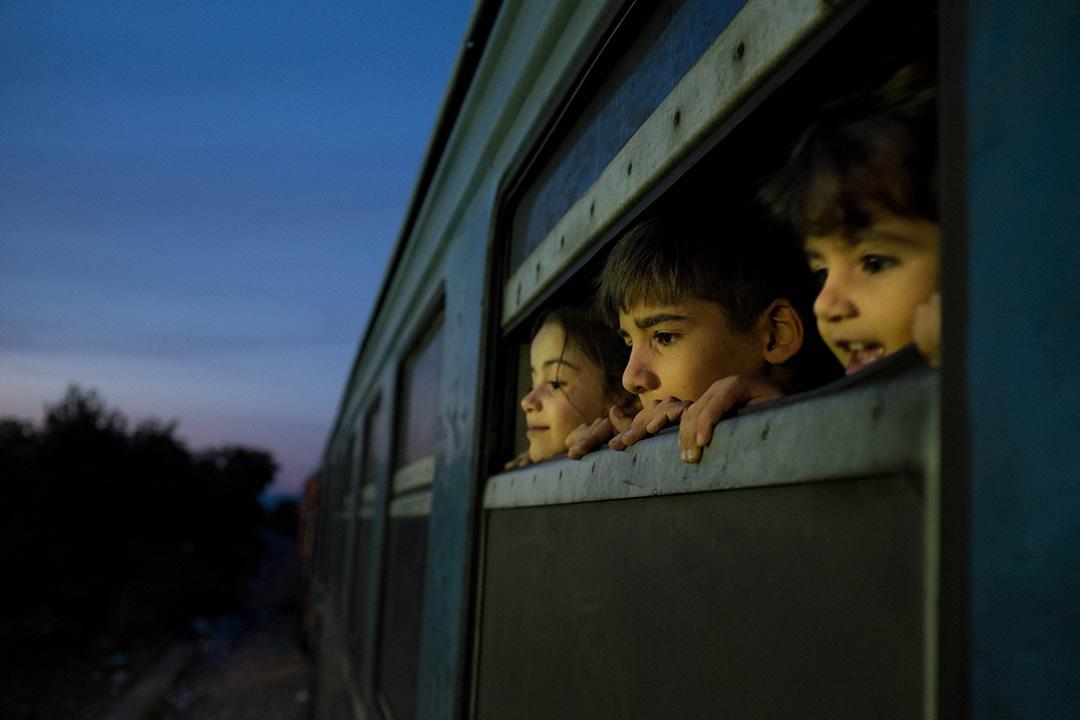 2015年10月2日,馬其頓,難民小童在蓋夫蓋利亞難民營乘搭火車時望出車窗外。蓋夫蓋利亞難民營每天接待約五千至一萬名難民,多數難民在此轉搭往塞爾維亞邊境的火車,繼續前往歐洲其他國家的旅程。攝:Ashley Gilbertson / VII Photo for UNICEF