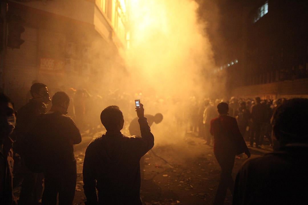 2011年11月23日,埃及開羅,一名青年在解放廣場,用手機拍下警方施放催淚彈後的情況。當時有大批示威者佔領解放廣場。攝:Peter Macdiarmid/GETTY