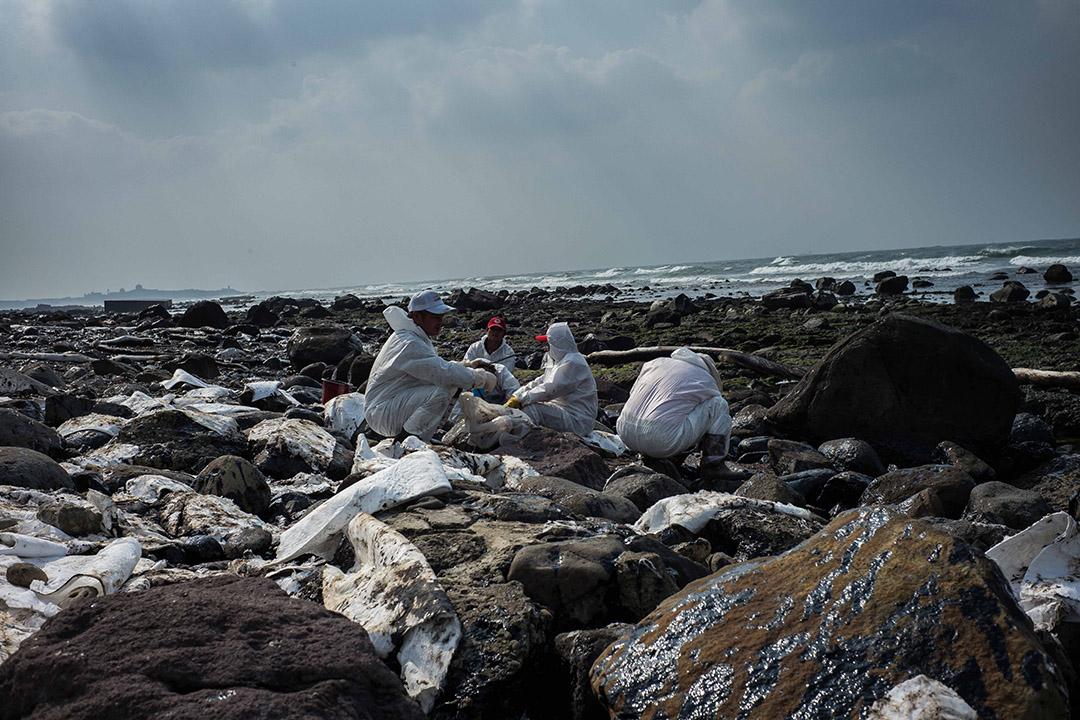 2016年3月26日,台灣北部石門,工人們在海岸清理「德翔台北」貨櫃輪漏出的油污。 攝: Billy H.C. Kwok/ 端傳媒