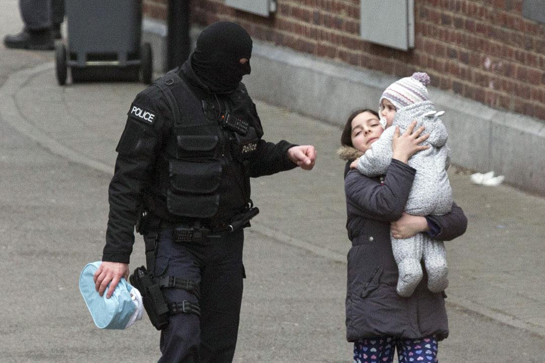 2016年3月18日,比利時布魯塞爾,警察在莫倫比克區追捕巴黎恐襲疑犯薩拉赫,期間疏散一名女子和嬰兒。攝:Geoffrey Van der Hasselt/AP