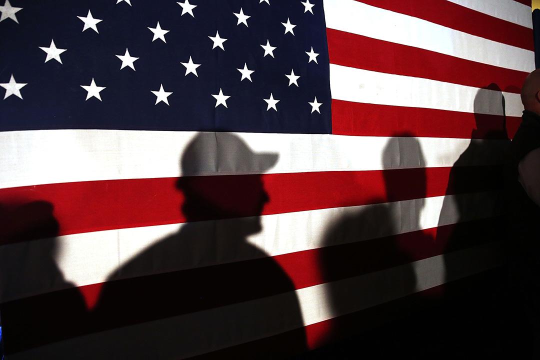 2016年2月11 日,美國,共和黨的支持者參與競選活動時,在一面美國旗前等候上台發 言。
