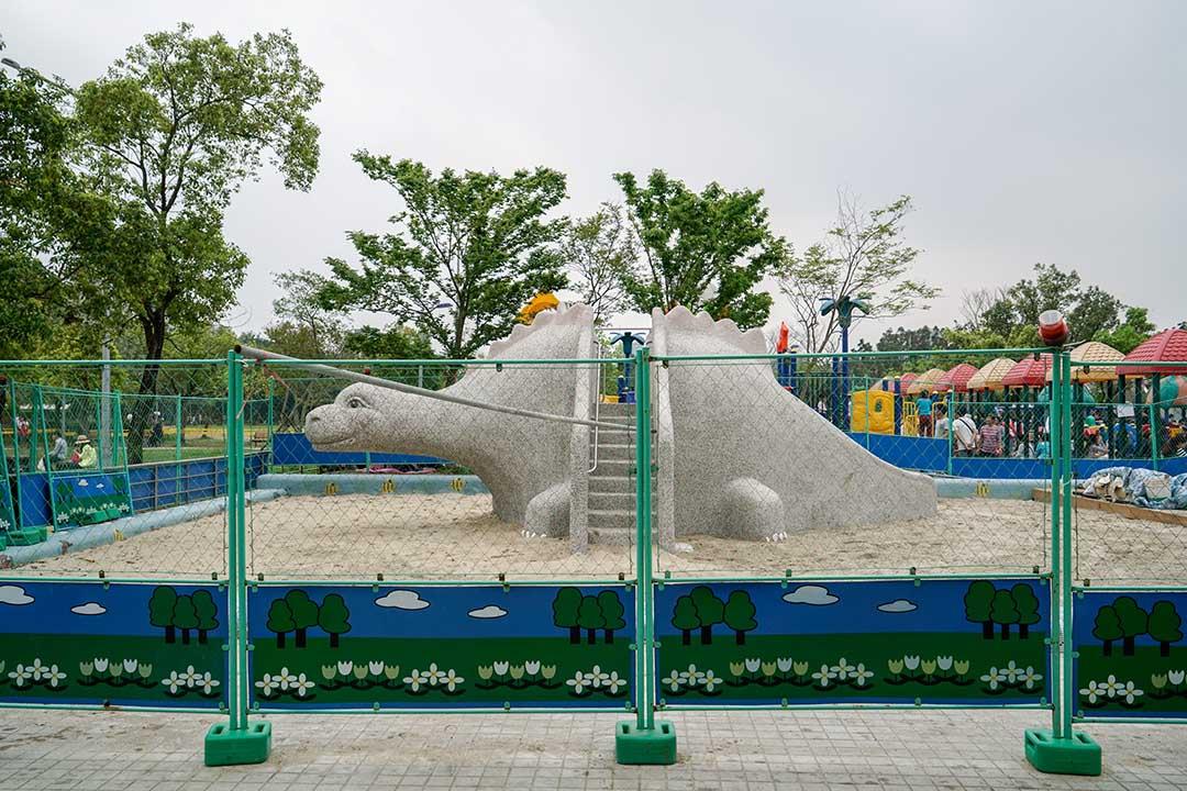 大安森林公園遊戲場原本規劃一座塑膠遊具所在處,在一群父母抗議之下,改為一組恐龍磨石子溜滑梯。攝:張國耀/端傳媒