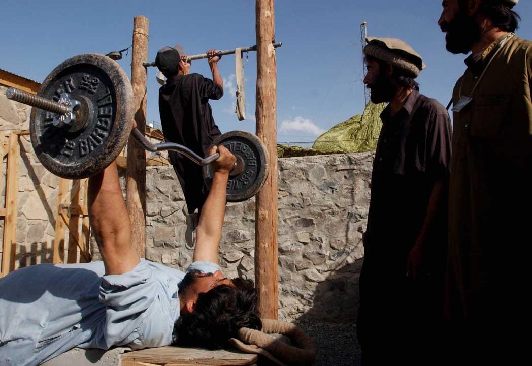 2002年9月15日,阿富汗,幾名阿富汗人在室外的建身設施建身。攝:Chris Hondros/Getty