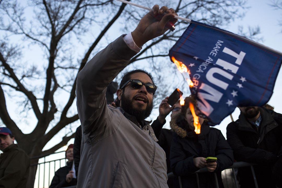 示威者在集會中焚燒特朗普的旗幟。攝 : Jonathan Gibby/GETTY