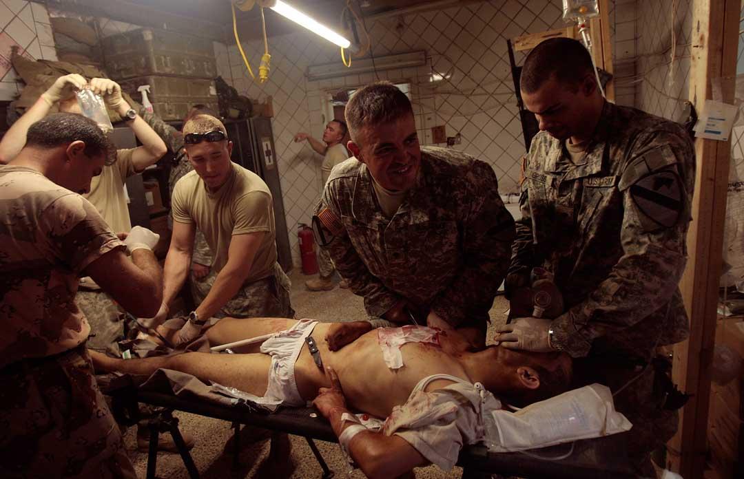 2007年6月29日,伊拉克巴格達,一名陸軍士兵被路邊炸彈炸傷,準備進行胸腔手術。攝:Chris Hondros/Getty
