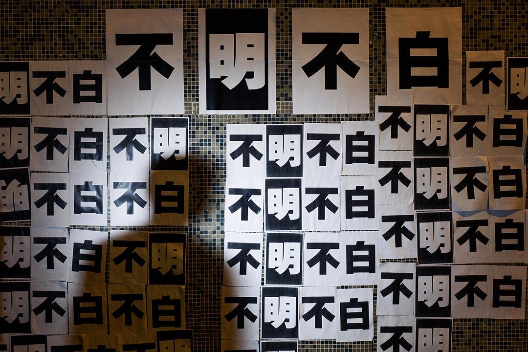 員工於明報集團大樓外牆張貼「不明不白」標語示威,表達對管理層決定的不滿。攝 : Anthony Kwan/端傳媒