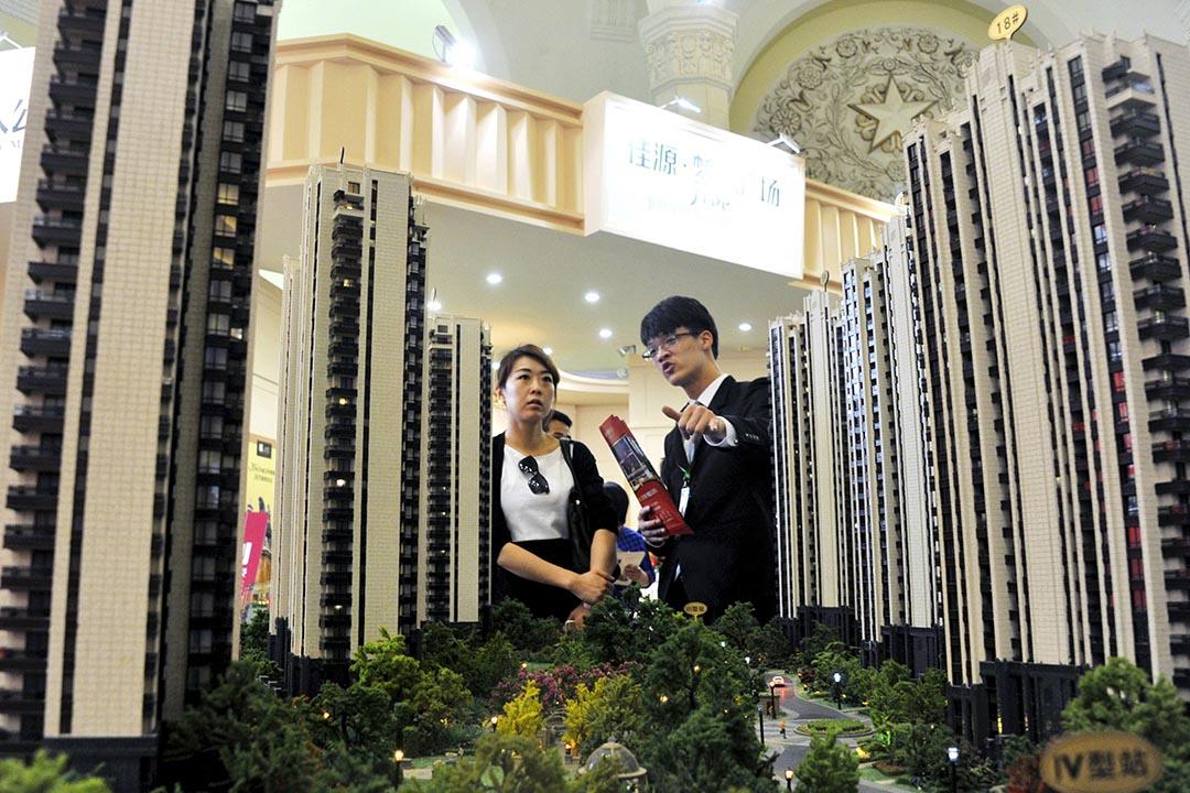 中國上海一個房地產展銷會,一名銷售員在住宅模型前向顧客推銷樓盤。攝:Stringer/REUTERS