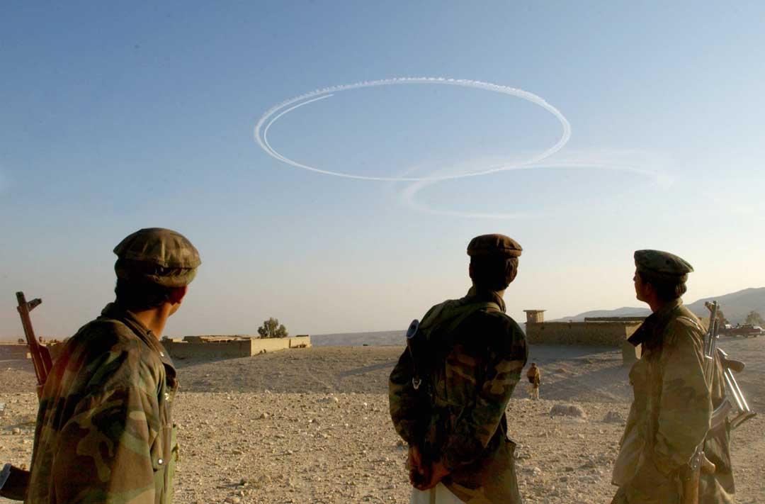 2002年9月15日,阿富汗,反塔利班士兵看著美國轟炸機在阿富汗托拉博拉地區飛過後留下的煙跡。攝:Chris Hondros/Getty