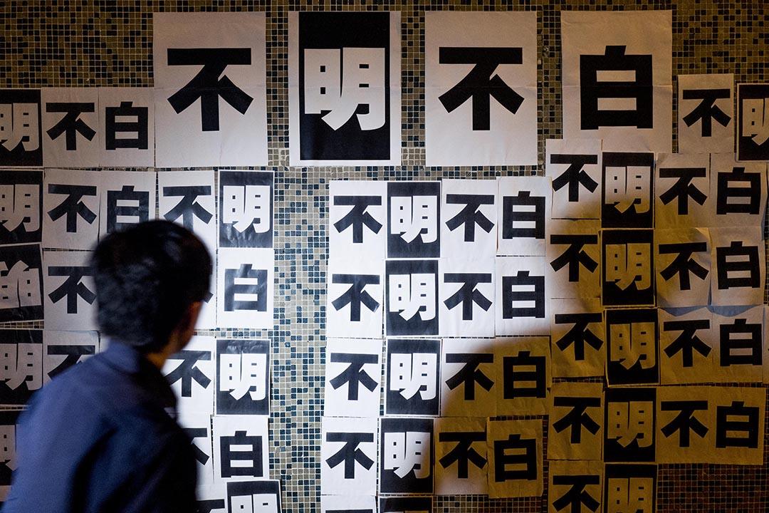 《明報》於4月20日凌晨,突然即時解僱執行總編輯姜國元。員工於當晚在明報集團大樓外牆張貼「不明不白」標語示威,表達對管理層決定的不滿。攝 : Anthony Kwan/端傳媒